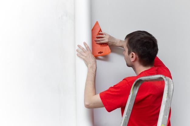 Giovane riparatore professionista che incolla sfondi sul muro di cemento concrete