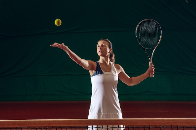 Giovane sportiva professionista giocando a tennis sulla parete del campo sportivo