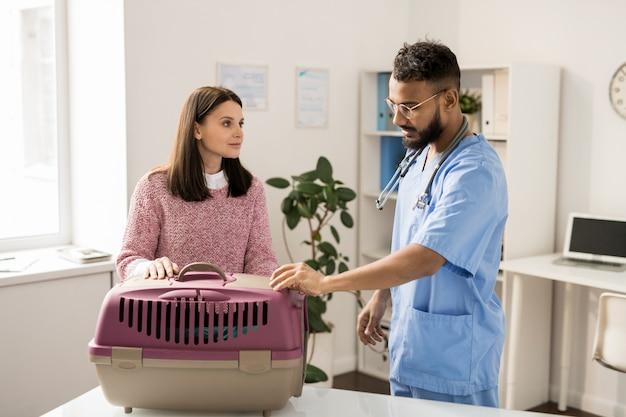 Giovane veterinario professionista che esamina animale domestico malato in trasportatore mentre parlando con proprietario grazioso nelle cliniche