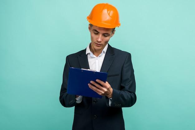 Un giovane professionista che indossa un cappello duro e portando un blocco per appunti su sfondo blu
