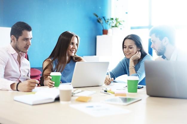 Giovani professionisti lavorano in ufficio moderno equipaggio d'affari che lavora con l'avvio sfocato, luci del sole