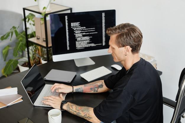 Giovane programmatore seduto al tavolo e digitando sul laptop che sviluppa software in ufficio