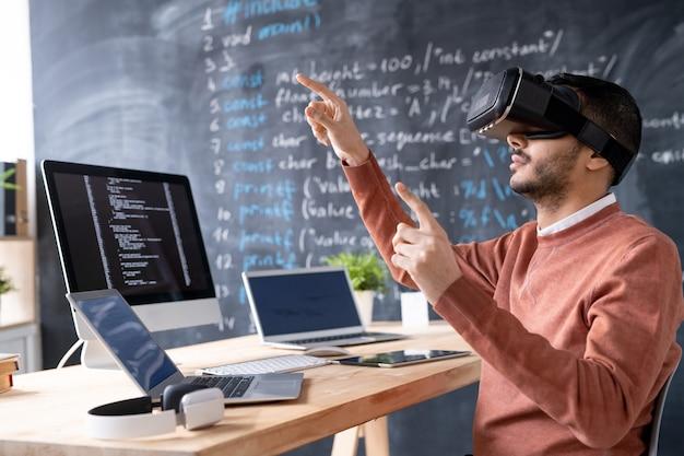 Giovane programmatore durante il test delle cuffie vr o la presentazione di nuovo software mentre indica il display virtuale sul posto di lavoro