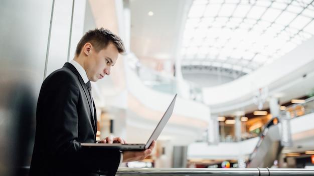 Giovane programmatore, lavorando su laptop, nel centro business, indoor, vista profilo, vestito in abito nero nel centro commerciale,