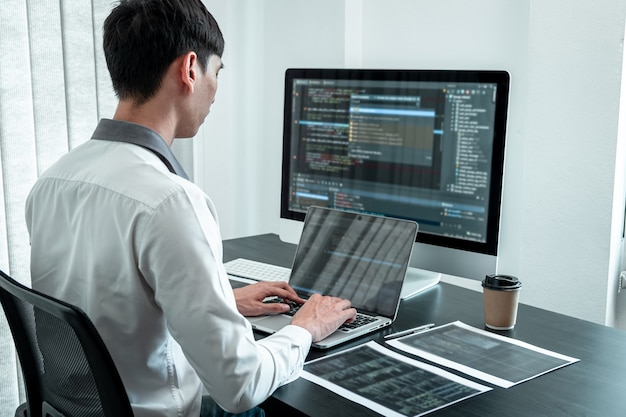 Giovane programmatore che lavora in computer javascript software in ufficio it, scrittura di codici e sito web di codici dati e tecnologie di database di codifica per trovare una soluzione al problema.