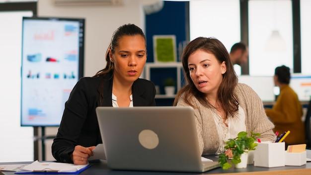 Giovane project manager e direttore dell'azienda che parla di strategia aziendale davanti al computer portatile in ufficio creativo. diversi team di colleghi che lavorano nel posto di lavoro di un'agenzia di marketing occupata.