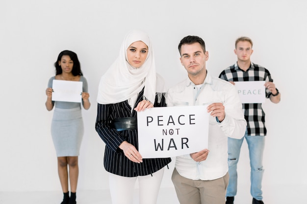 Giovani manifestanti, donna musulmana e uomo caucasico, cantando per salvare la pace, con in mano un poster senza slogan di guerra