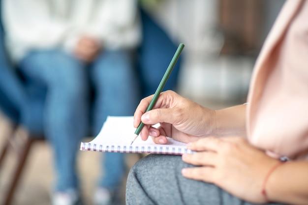 Giovane psicoterapeuta che prende appunti da un paziente