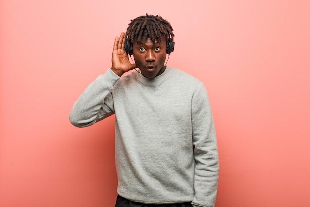 Giovane uomo di colore rasta ascoltando musica con le cuffie cercando di ascoltare un pettegolezzo.