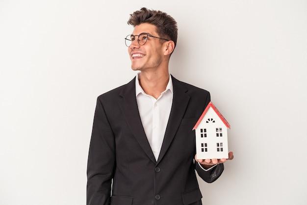 Giovane agente immobiliare caucasico isolato su sfondo bianco che sogna di raggiungere obiettivi e scopi