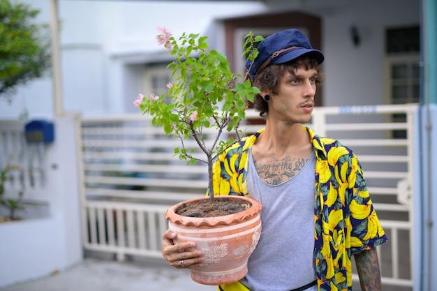 Il giovane uomo ribelle che pensa mentre tiene il vaso dei fiori supera