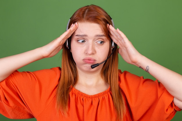 La giovane donna dai capelli rossi in camicetta arancione casual sul call center del call center del gestore della parete verde lavora con le cuffie parla stanco esaurito