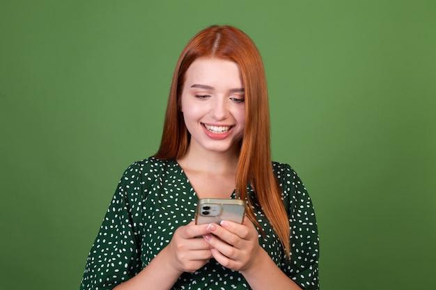 Giovane donna dai capelli rossi sulla parete verde con messaggi di testo sul cellulare che chiacchierano con un sorriso sul viso, felice positivo