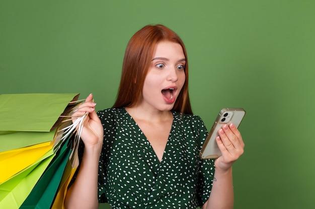 Giovane donna dai capelli rossi sulla parete verde con borse della spesa e telefono cellulare scioccata stupita