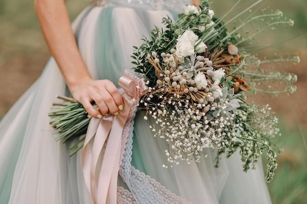 Giovane sposa dai capelli rossi che tiene un bouquet da sposa primaverile