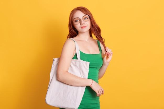 Giovane ragazza dai capelli rossi con il sacchetto di tote del cliente di cotone vuoto bianco che indossa la maglietta verde