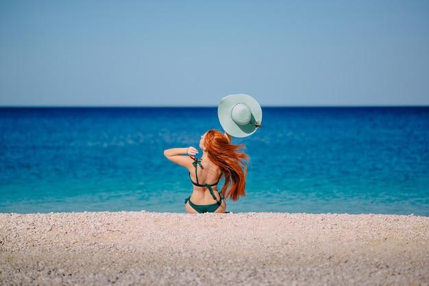 Giovane donna dai capelli rossi in un cappello e un bikini si siede sulla spiaggia in una giornata di sole