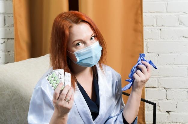 La giovane donna dai capelli rossi nella mascherina medica tiene le pillole e i guanti di gomma nelle sue mani. il concetto ha messo in quarantena il trattamento del coronavirus, la malattia.