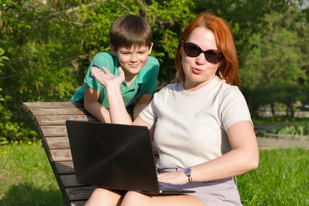 Giovane donna dai capelli rossi nel parco con il suo piccolo figlio. la mamma è indignata perché suo figlio interferisce con il suo lavoro. donna con laptop che cerca di lavorare nel parco e combinare lavoro e camminare con un bambino