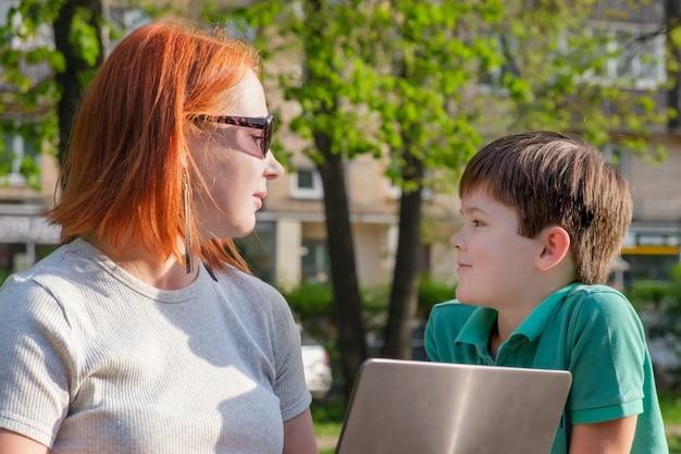 Giovane donna dai capelli rossi nel parco con il suo piccolo figlio nel parco. mamma e figlio si guardano. donna con laptop che cerca di lavorare nel parco e combinare lavoro e camminare con un bambino