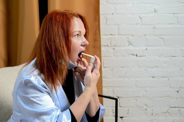 La giovane donna dai capelli rossi tratta lo spray per la gola. concetto: trattamento dei primi segni di raffreddore, malattie virali stagionali, influenza. spazio per il testo