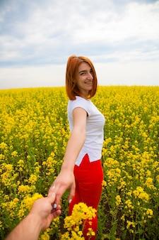 Una giovane donna dai capelli rossi con una maglietta bianca e jeans rossi sorride e conduce la mano bagnata dell'uomo verso le avventure di un enorme campo di fiori gialli in una calda giornata estiva, seguimi