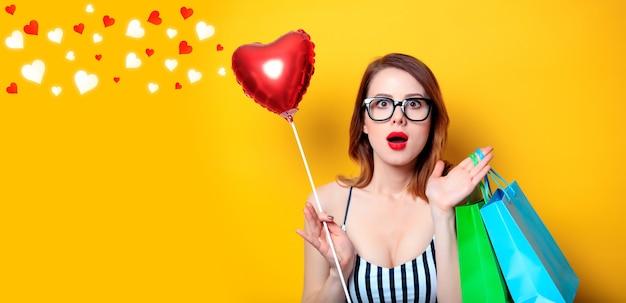 Giovane donna dai capelli rossi con giocattolo a forma di cuore e borse della spesa su sfondo giallo
