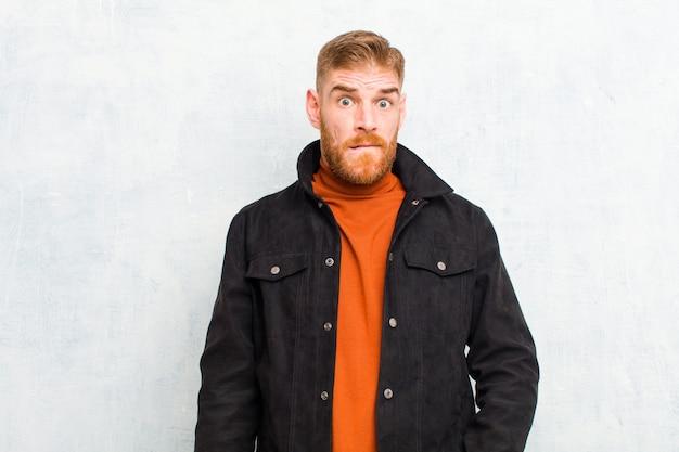 Giovane uomo testa rossa sentirsi all'oscuro, confuso e incerto su quale opzione scegliere, cercando di risolvere il problema contro il muro del grunge