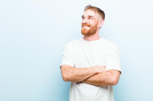 Giovane uomo testa rossa sentirsi felice, orgoglioso e pieno di speranza, chiedendosi o pensando, alzando lo sguardo per copiare lo spazio con le braccia incrociate su sfondo blu morbido