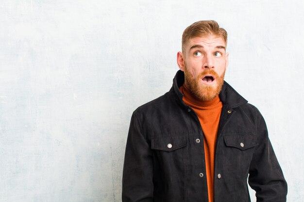 Giovane uomo testa rossa sentirsi scioccato, felice, stupito e sorpreso, guardando al lato con la bocca aperta contro il muro del grunge