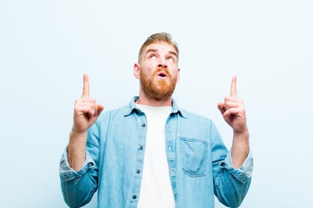 Giovane uomo rosso che sembra scioccato, stupito e con la bocca aperta, rivolto verso l'alto con entrambe le mani