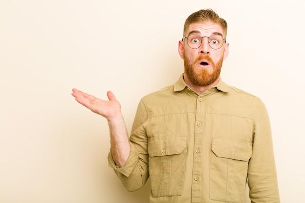 Giovane uomo testa rossa che sembra sorpreso e scioccato, con la mascella caduta in possesso di un oggetto con una mano aperta sul lato sul muro beige