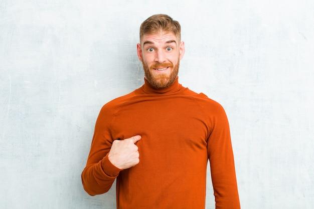 Giovane uomo capo rosso che indossa il collo di tartaruga che sembra scioccato e sorpreso con la bocca spalancata, indicando sé contro il muro di cemento