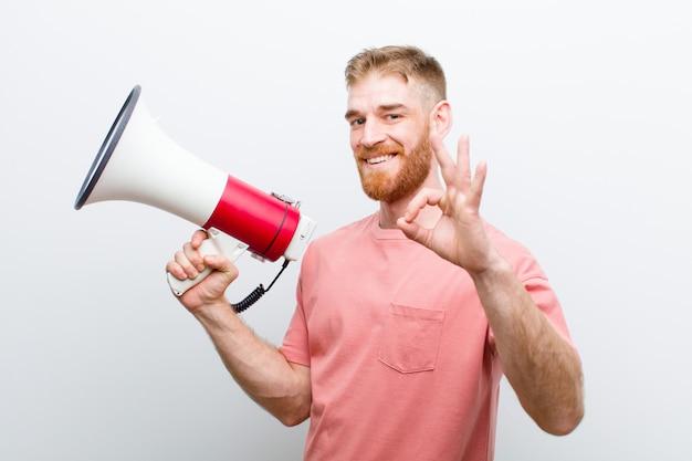 Giovane uomo capo rosso con un megafono su sfondo bianco