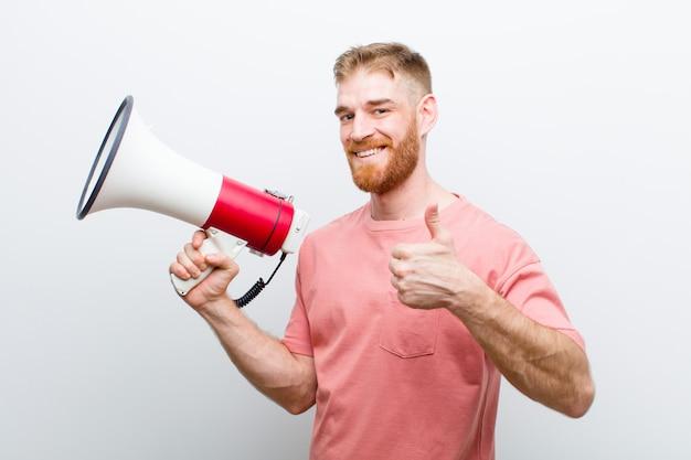 Giovane uomo capo rosso con un megafono contro bianco