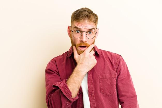 Giovane uomo testa rossa con la bocca e gli occhi ben aperti e la mano sul mento, sentendosi spiacevolmente scioccato, dicendo cosa o wow su sfondo beige