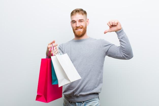 Giovane uomo testa rossa con borse della spesa