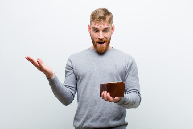 Giovane uomo capo rosso con un portafoglio contro fondo bianco