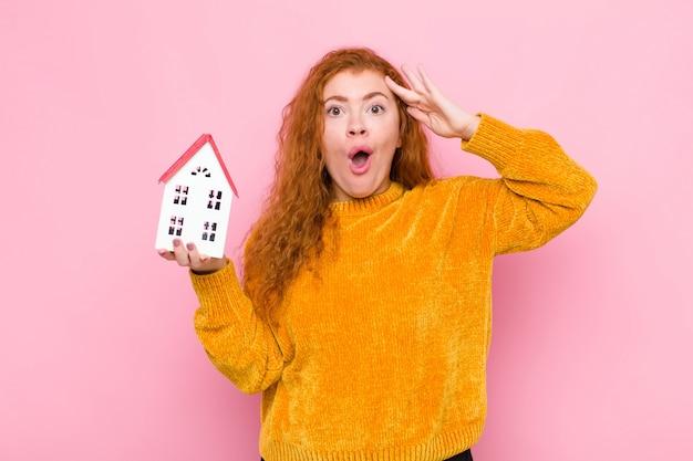 Giovane donna dai capelli rossi che sembra felice, stupita e sorpresa, sorridente e realizzando sorprendenti e incredibili buone notizie con un modello di casa