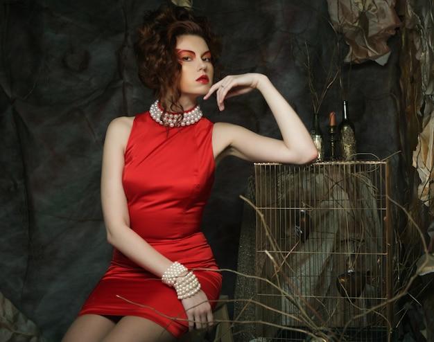 Redhair giovane donna con volto creativo che indossa un abito rosso