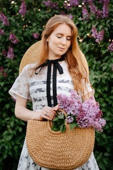 Una giovane ragazza dai capelli rossi con un cappello tiene in mano una borsa di vimini con lillà viola in fiore di verde in primavera