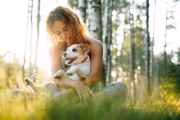 Giovane donna dai capelli rossi seduta sull'erba verde nel parco tenendo in braccio il cane jack russell