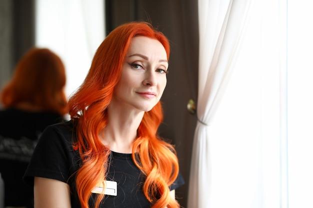 Giovane donna dai capelli rossi che si allena in un salone di bellezza ritratto di una spa professionale femminile