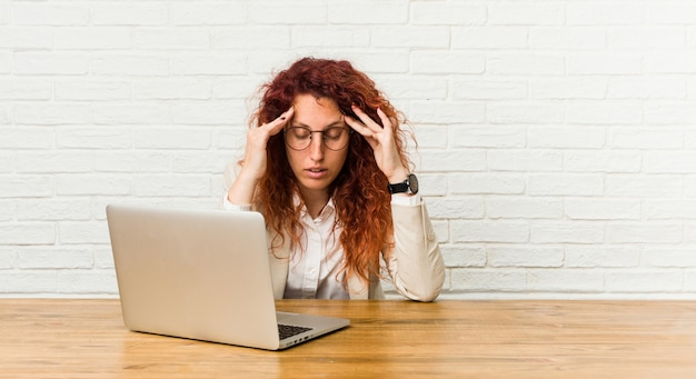 Donna riccia della giovane testarossa che lavora con le sue tempie commoventi del suo computer portatile e che ha mal di testa.