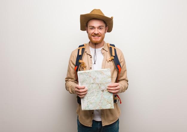 Uomo giovane esploratore di redhead allegro con un grande sorriso. in possesso di una mappa.