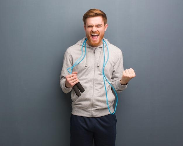 Giovane uomo di forma fisica della testarossa sorpreso e scioccato. sta tenendo una corda per saltare.