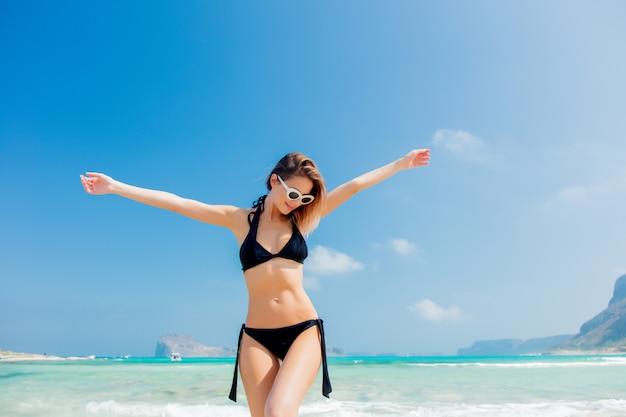 Giovane ragazza rossa in bikini nero sulla spiaggia di balos
