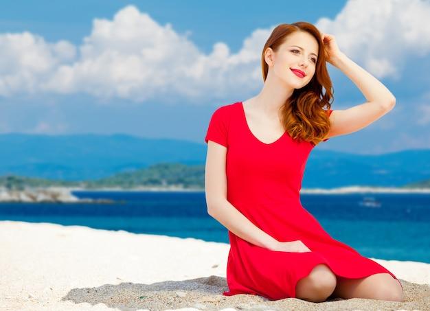 La giovane ragazza della testarossa in vestito rosso ha un resto sulla spiaggia del mare di estate