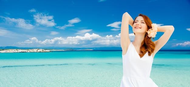La giovane ragazza della testarossa in vestito bianco e fiore nei capelli ha un resto sulla spiaggia del mare di estate