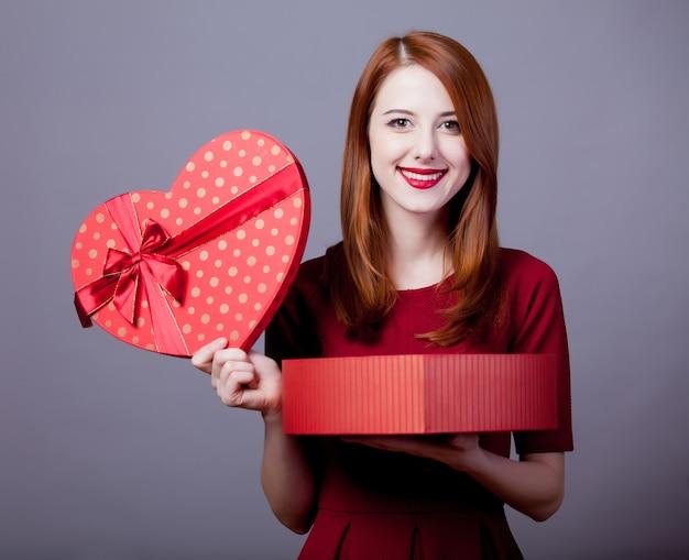 Giovane ragazza della testarossa con la scatola di forma del focolare su gray.